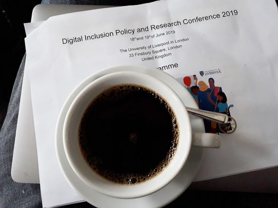 A cup of coffee sits on top of a stack of papers, a laptop and the programme for the DIPRC conference on Angela's lap.