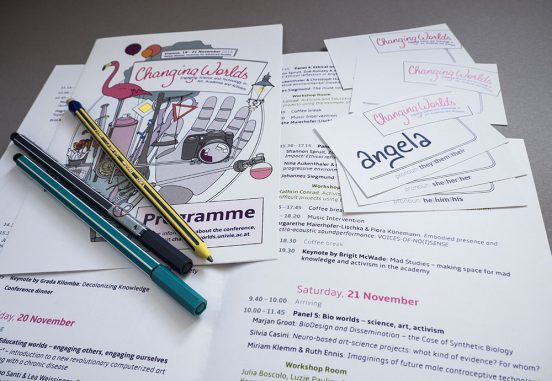 A few programmes and nametags (with pre-printed pronoun options) arranged on a desk with some pencils