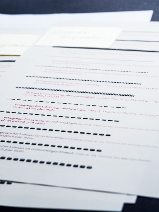 Close up of swell paper with black, 3D lines and flat red writing.