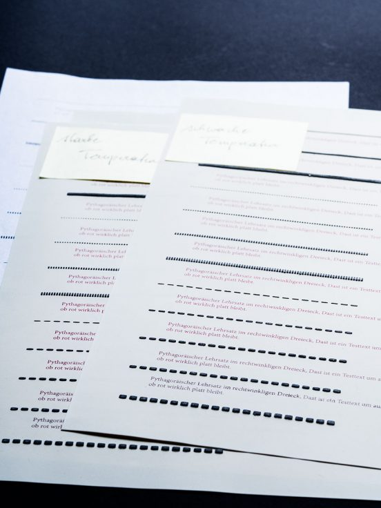 Pages of swell paper with test lines in different line styles and red writing in different shades that has stayed flat in the swelling process